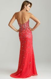 Style 6745: This strapless sweetheart Night Moves style is perfect for prom 2015, pageants, and quinceañeras. Heavily beaded over the bodice with rhinestones and mirrored triangle pieces, the beading lessens as it streams down the dress. A slit over the left leg adds some flair to this watermelon-colored style. Due to all of the beading over this dress, this style photographs amazingly as all of the beads capture and reflect the light.