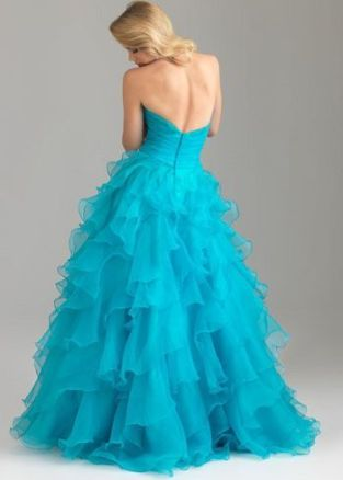 6400: Here's that strapless, sweetheart ballgown you've been looking for! Tiers of chiffon ruffles cascade down this dress from its princess waistline, making the motions of this style look ethereal. The crystallized flower embellishment on the left side of this dress adds a little shine to this style, making it a perfect dress for a prom, pageant, or quinceañera.